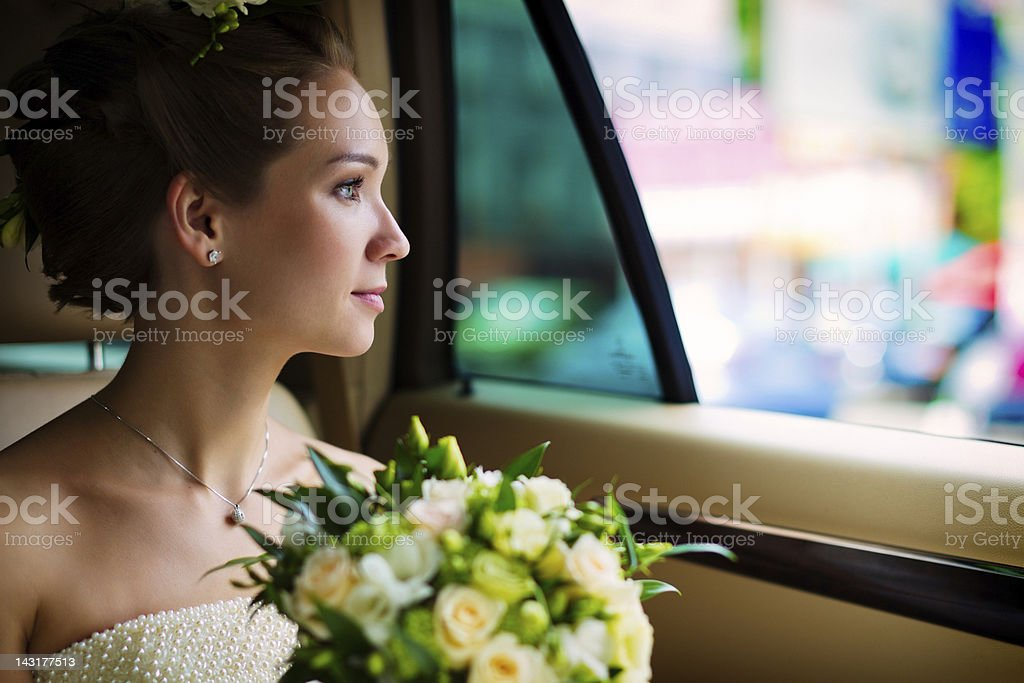 Young bride sitting in the car stock photo