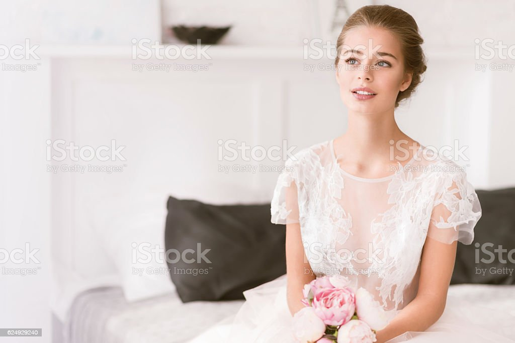Young bride sitting on the bed at home stock photo