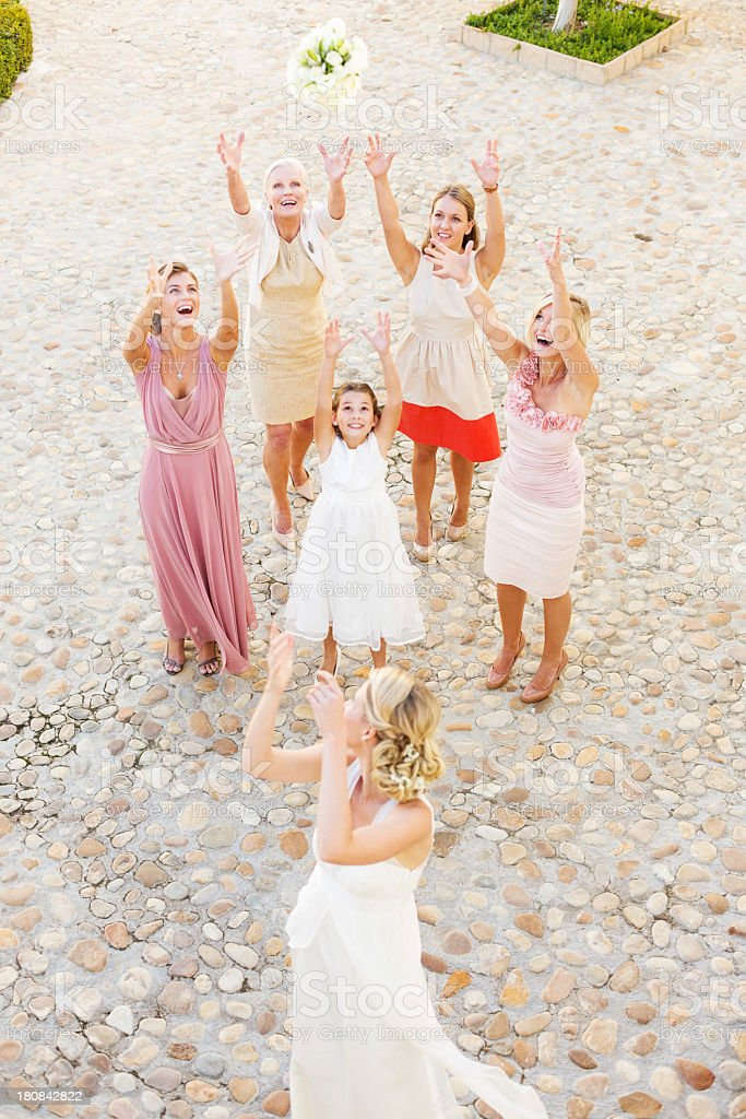 Young Bride Throwing Bouquet Of Flowers At Guests stock photo