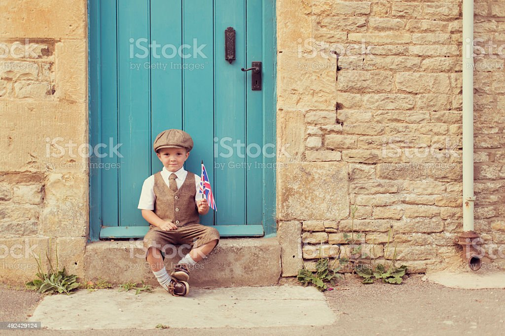 Young British Boy Sits on Doorstep With Union Jack stock photo