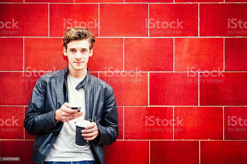 Young British man portrait against red wall stock photo