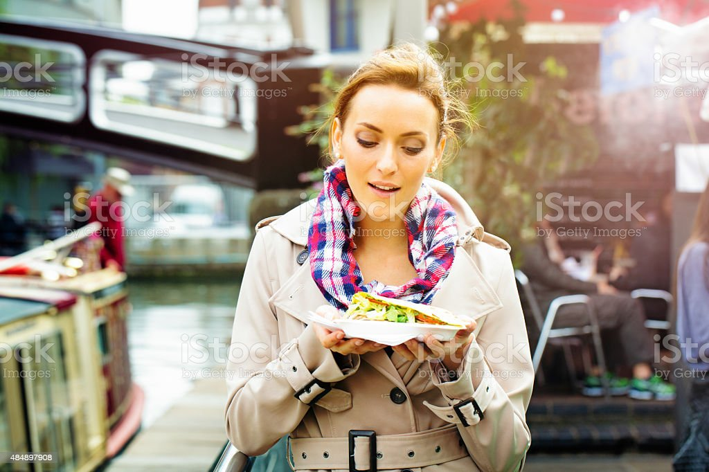 Young British woman looks at take-out food with appetite stock photo