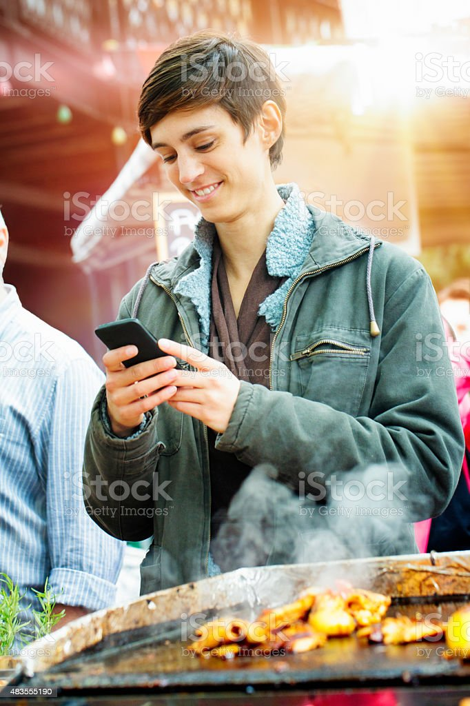 Young British woman smiles at phone while waiting for lunch stock photo