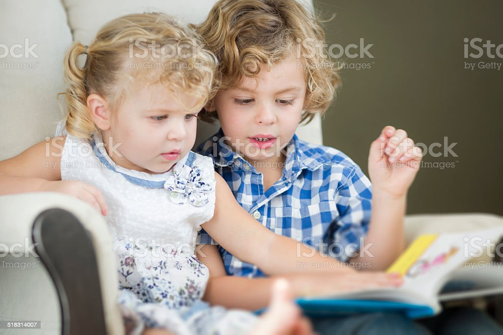 Young Brother and Sister Reading a Book Together stock photo