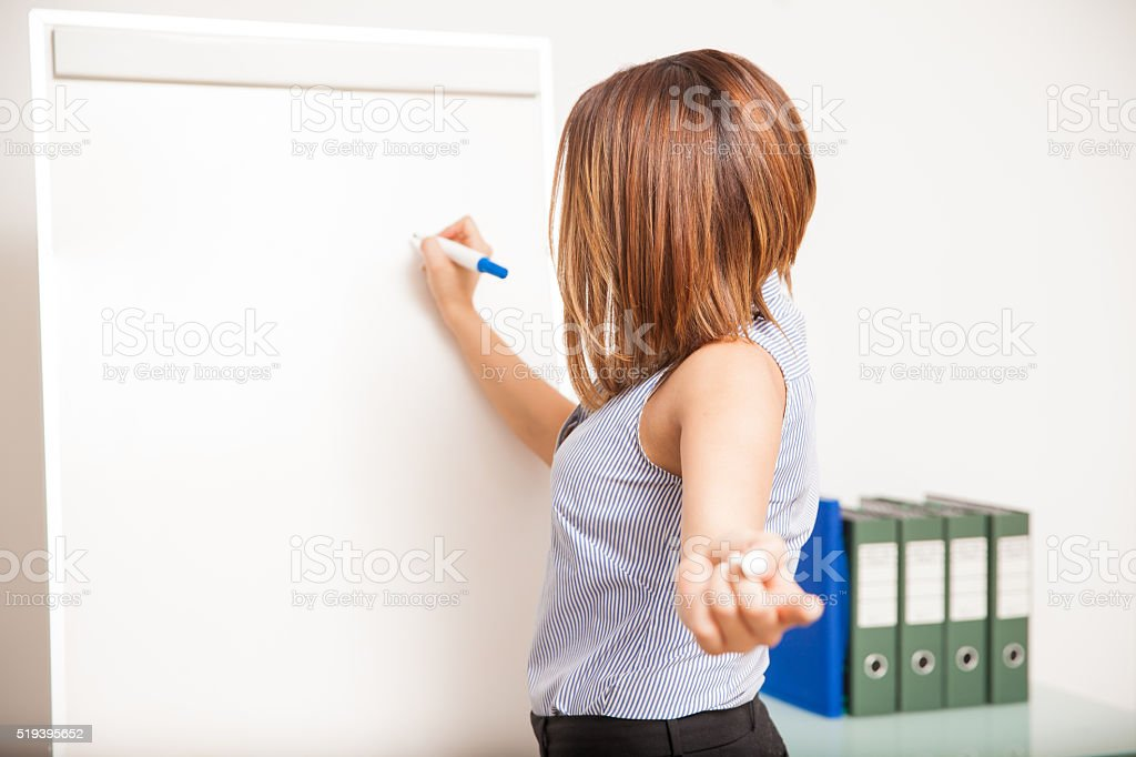 Young brunette asking a question to her class stock photo