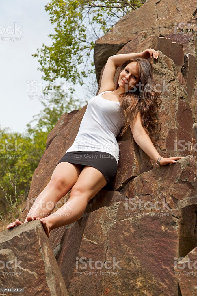 Young brunette between a rocks stock photo