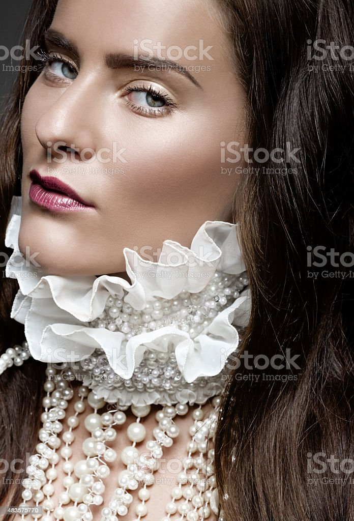 Young brunette female model wearing pearl jewellery stock photo