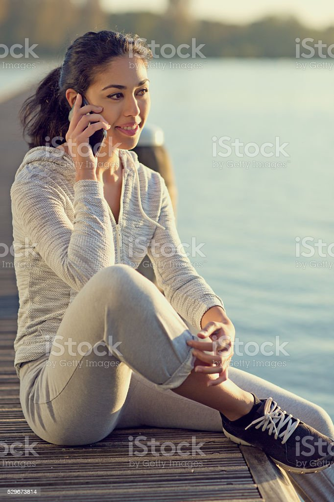 Young brunette female using smartphone at lakeside pier stock photo