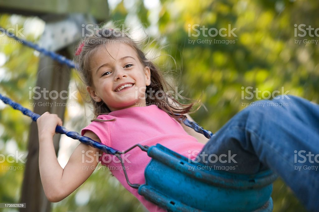 A young brunette girl in a pink shirt smiles as she swings royalty-free stock photo