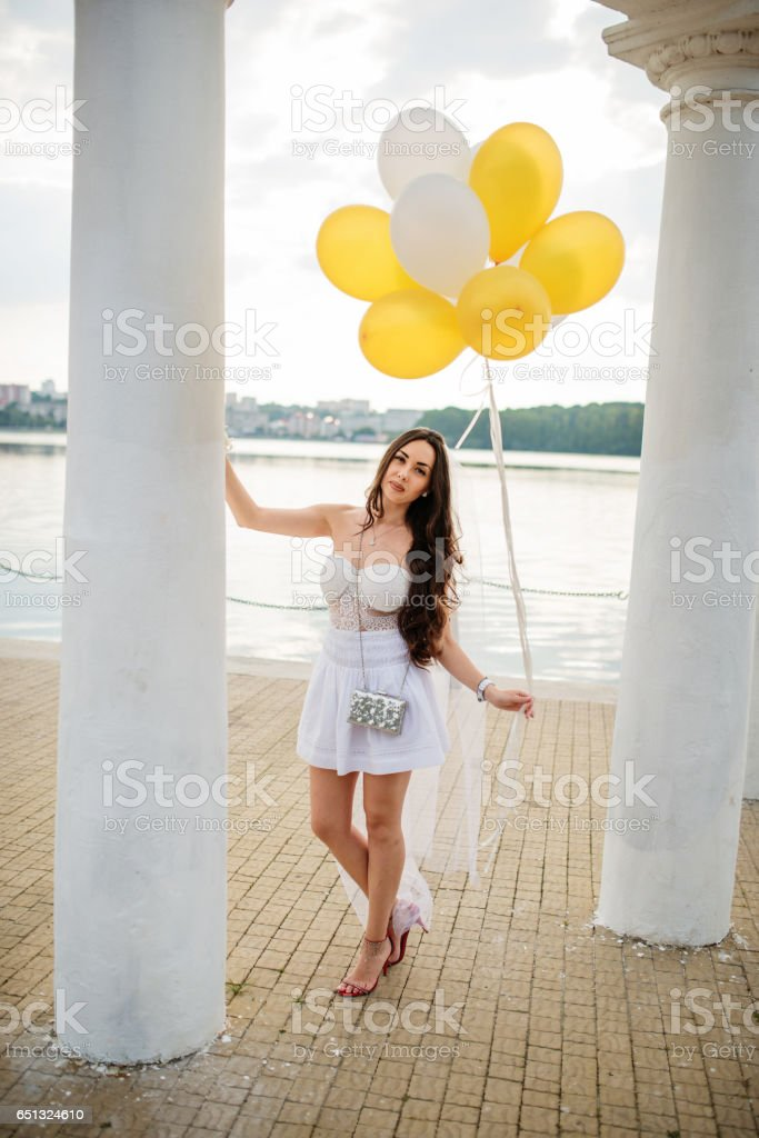 Young brunette girl with balloons at hand weared on white dress on hen party against white columns of arch. stock photo
