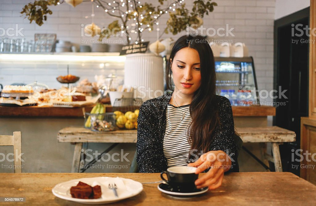 Young brunette having a coffee and a chocolate cake stock photo