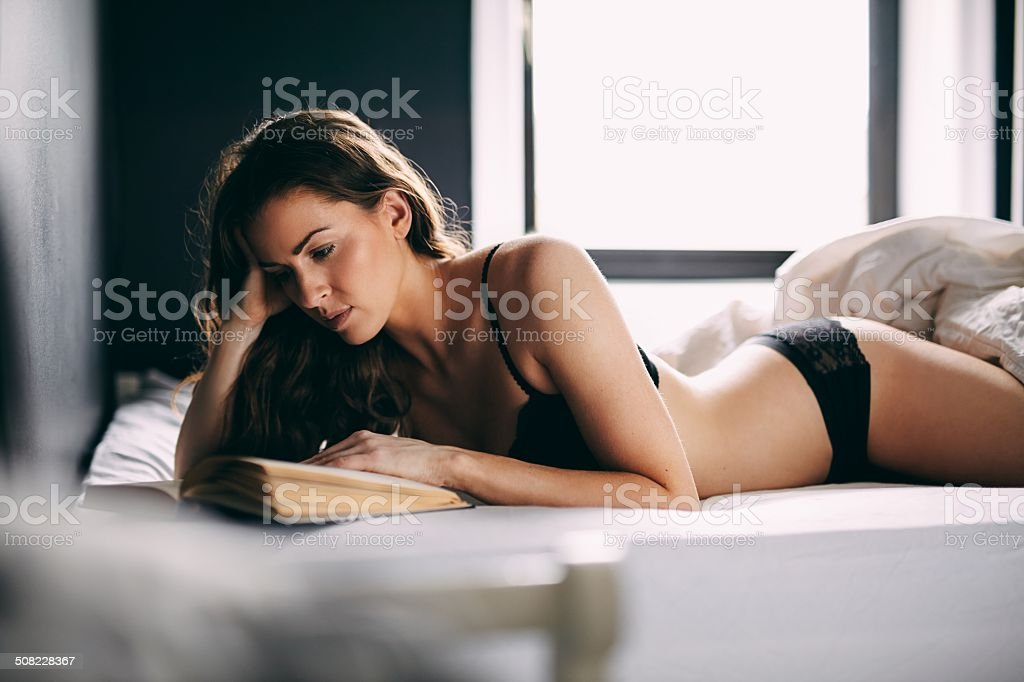 Young brunette in lingerie reading novel on bed stock photo