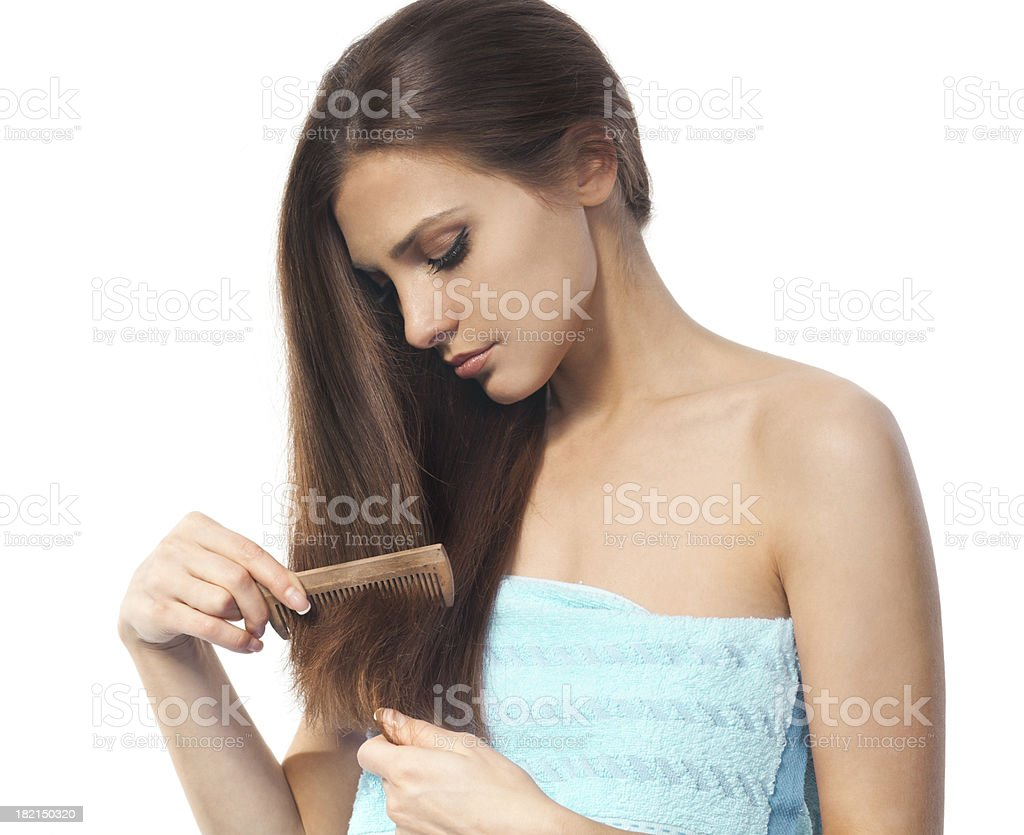 Young brunette lady combing her beautiful long hair royalty-free stock photo