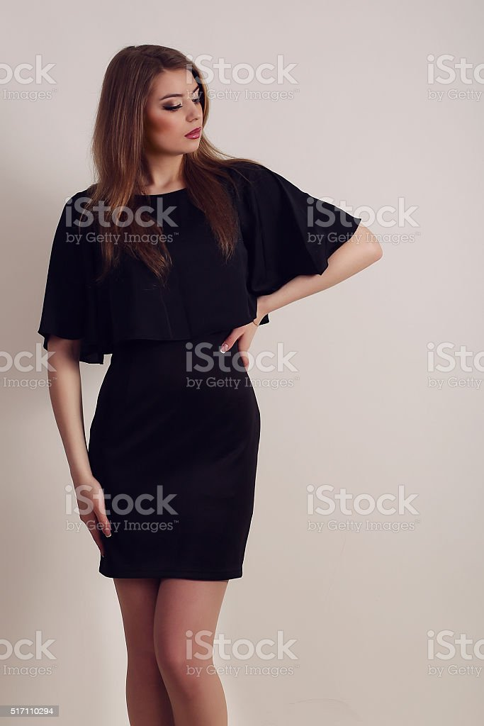 Young brunette lady in black dress posing on grey background royalty-free stock photo