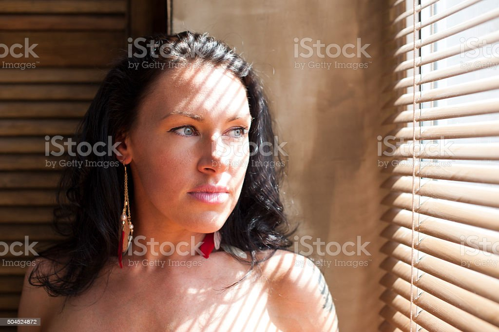 Young brunette looking out the window through blinds stock photo