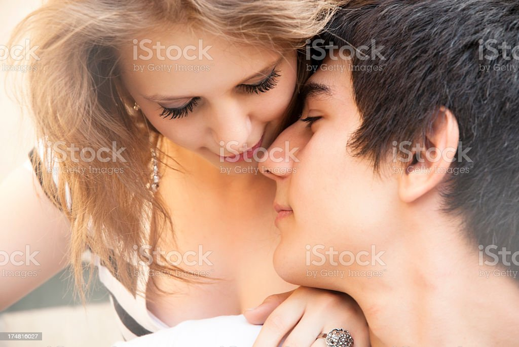 A young brunette man and blonde woman snuggling lovingly stock photo