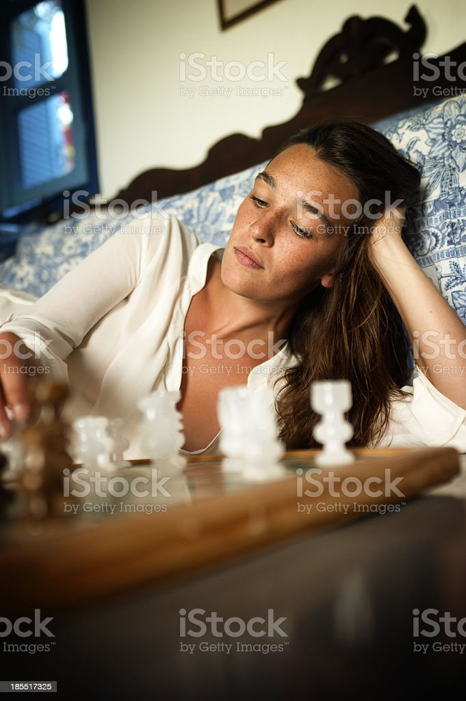 Young brunette playing chess royalty-free stock photo