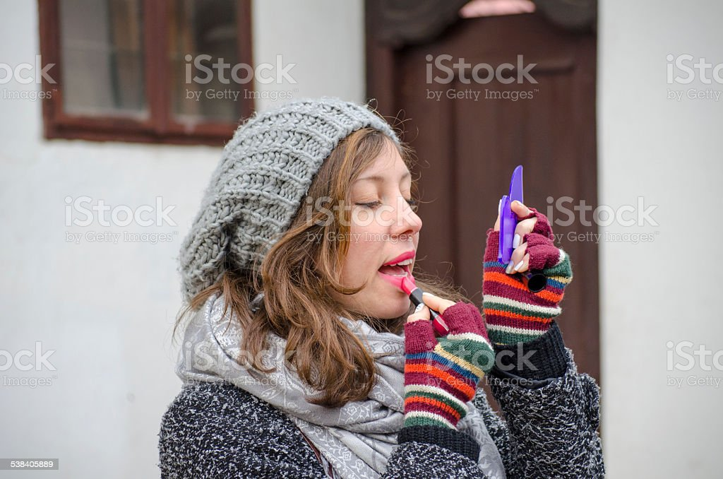 Young brunette putting lipstick on royalty-free stock photo