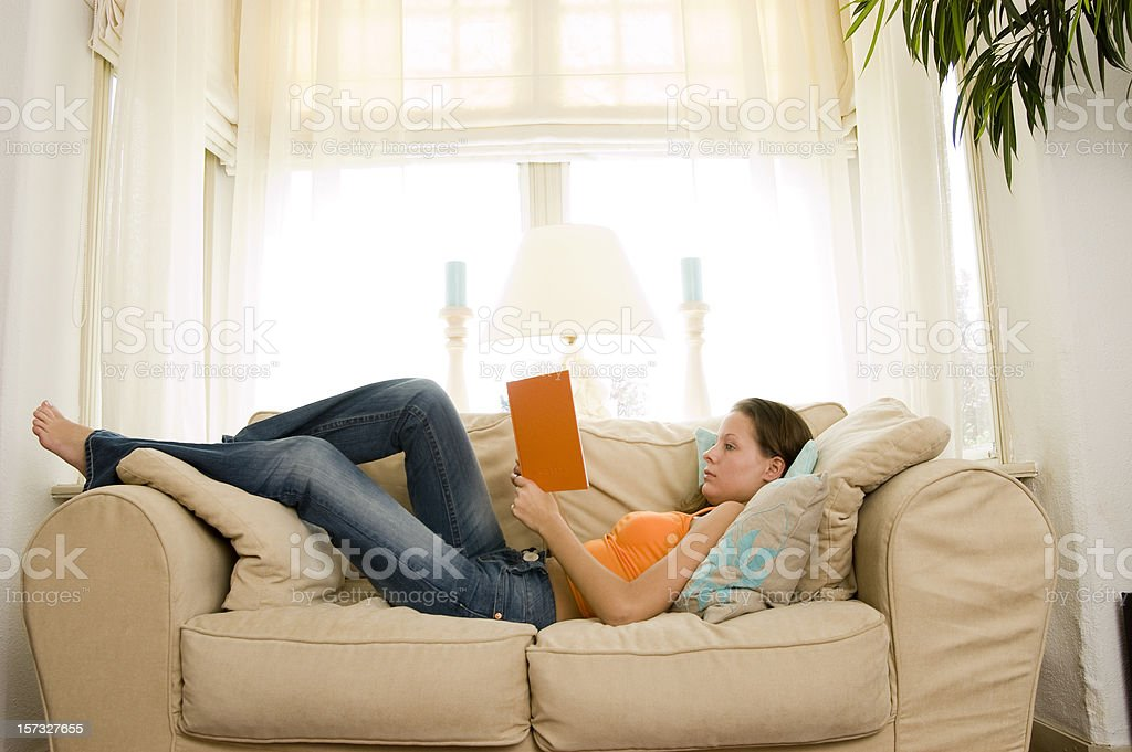 young brunette reading a book on the sofa royalty-free stock photo