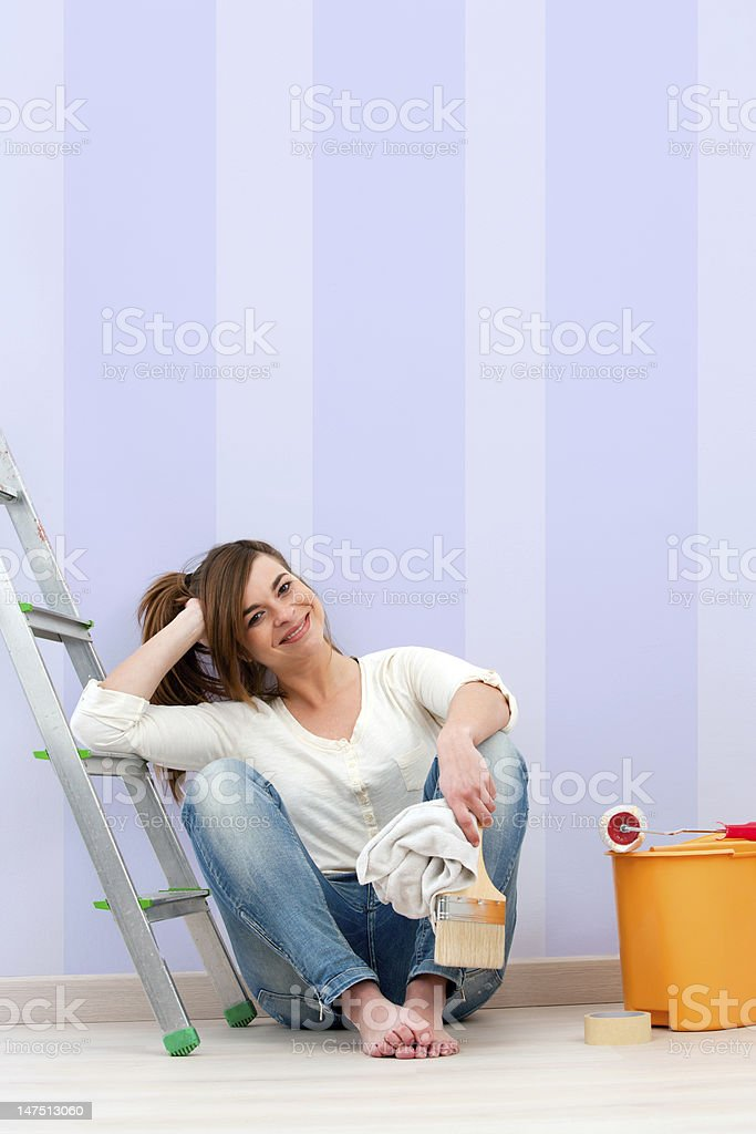 Young brunette sitting on floor after painting. stock photo