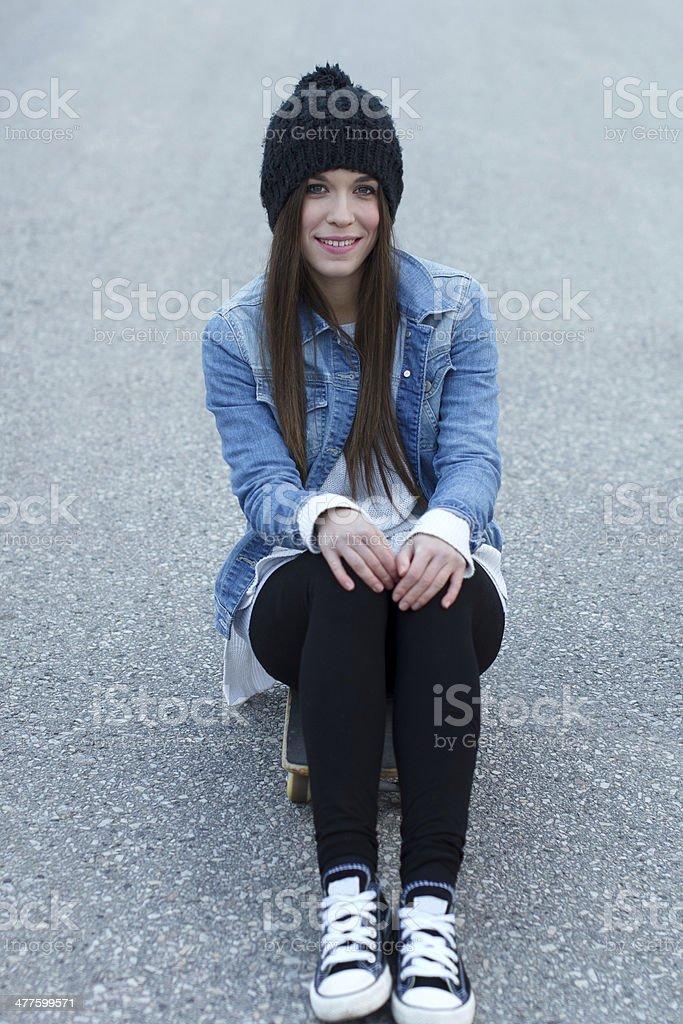 Young brunette skateboarder girl sitting on skateboard royalty-free stock photo
