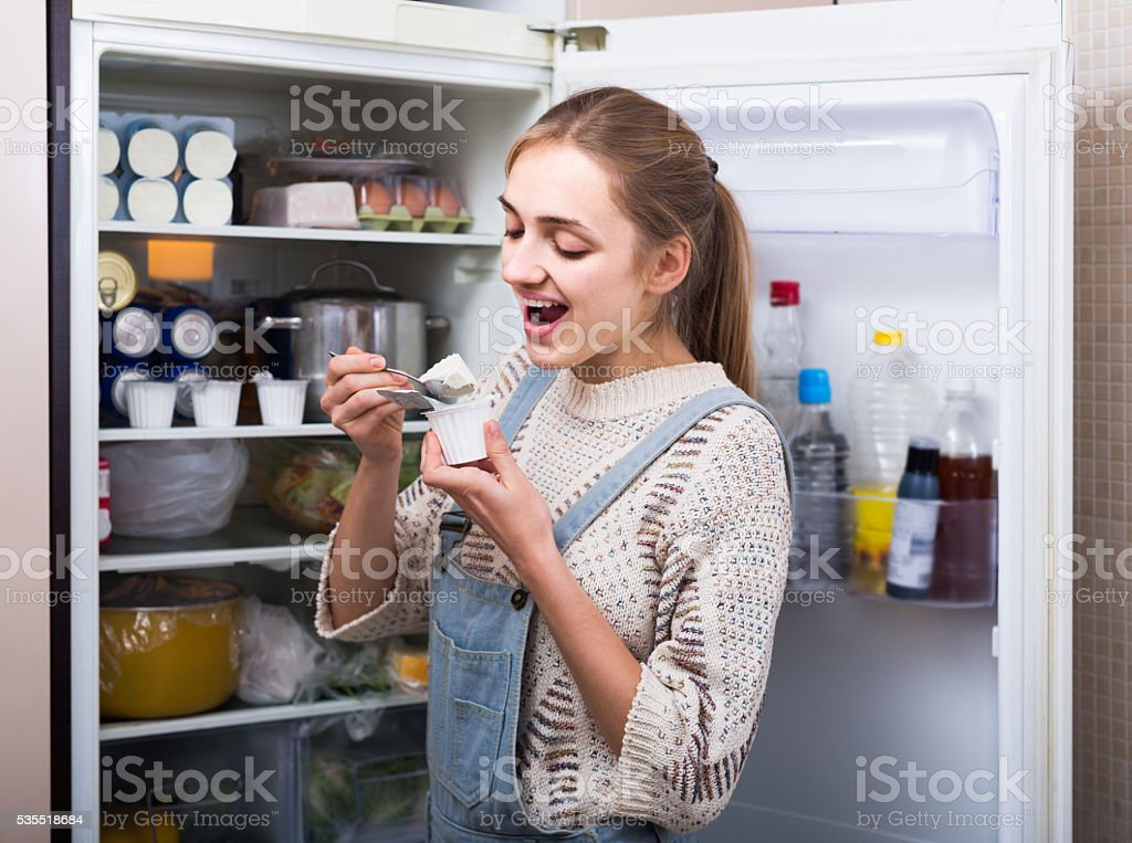young brunette standing near fridge with soft cheese stock photo
