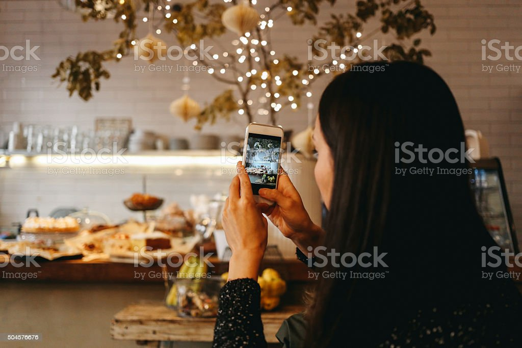 Young brunette taking a photo with a smartphone stock photo