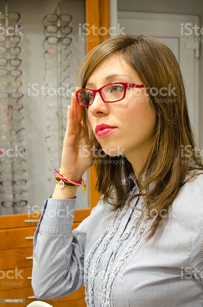 Young brunette trying glasses at the optics store royalty-free stock photo