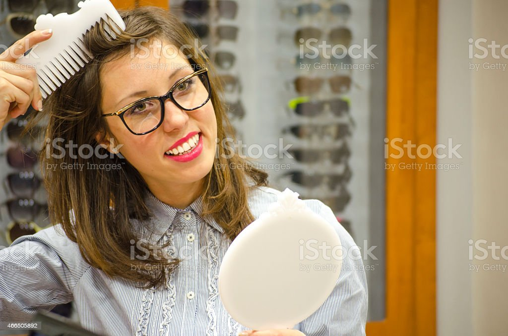 Young brunette trying glasses in front of a mirror royalty-free stock photo