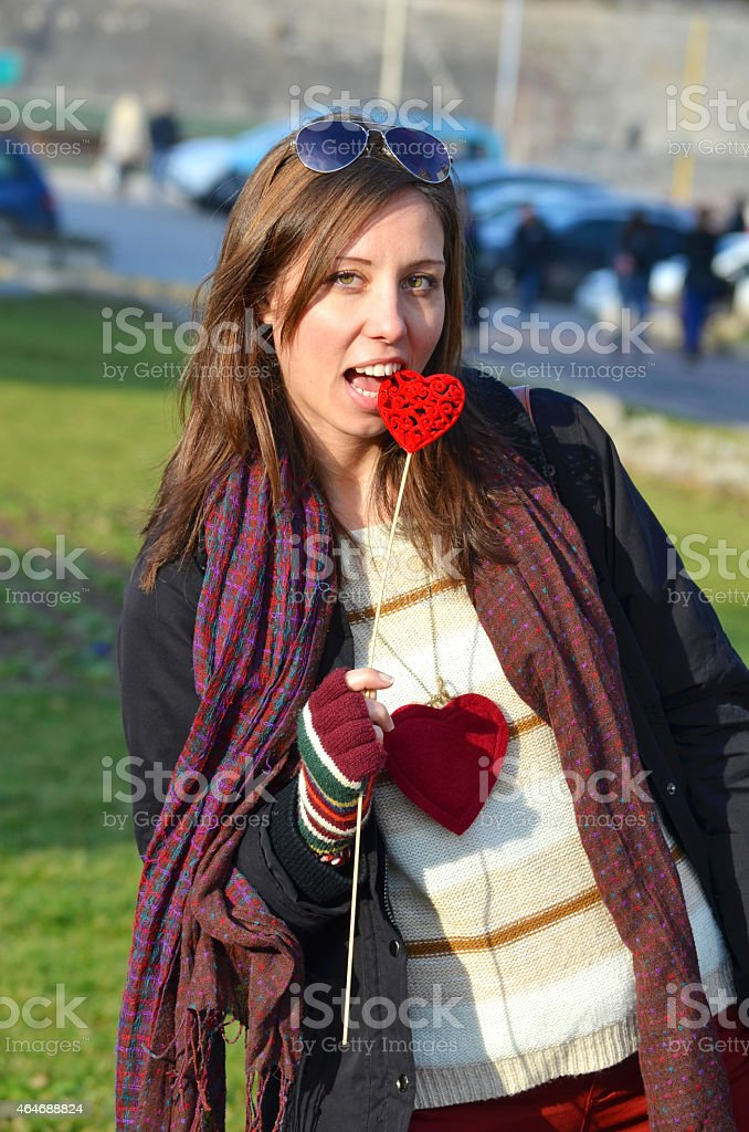 Young brunette with a heart in her teeth royalty-free stock photo