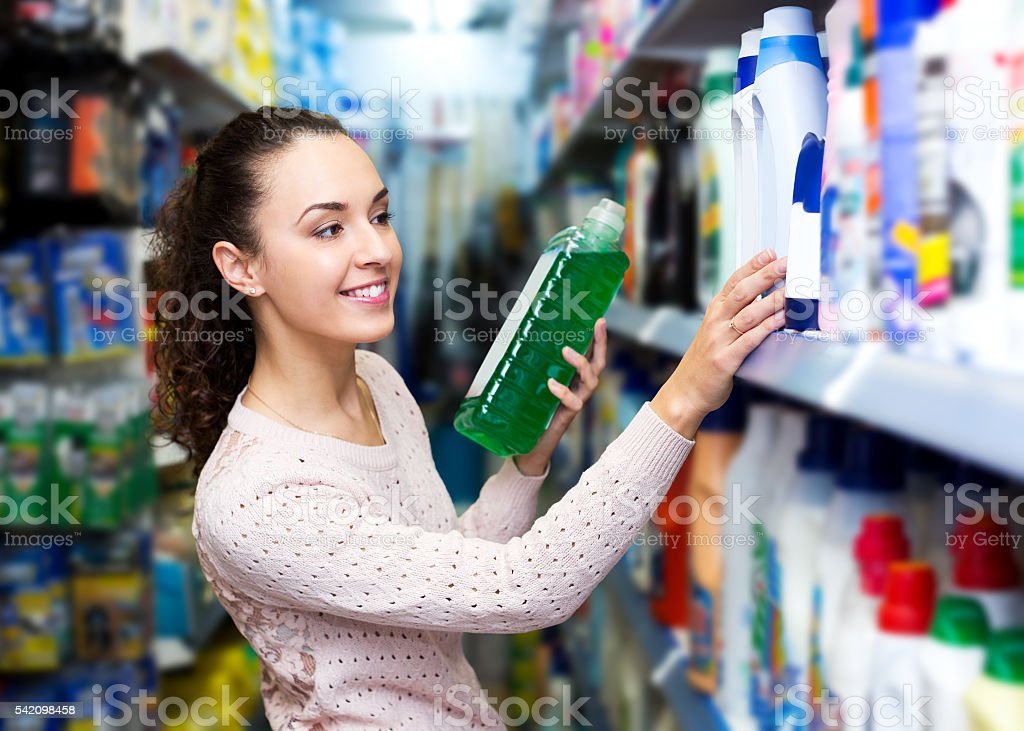 Young brunette woman choosing detergent stock photo