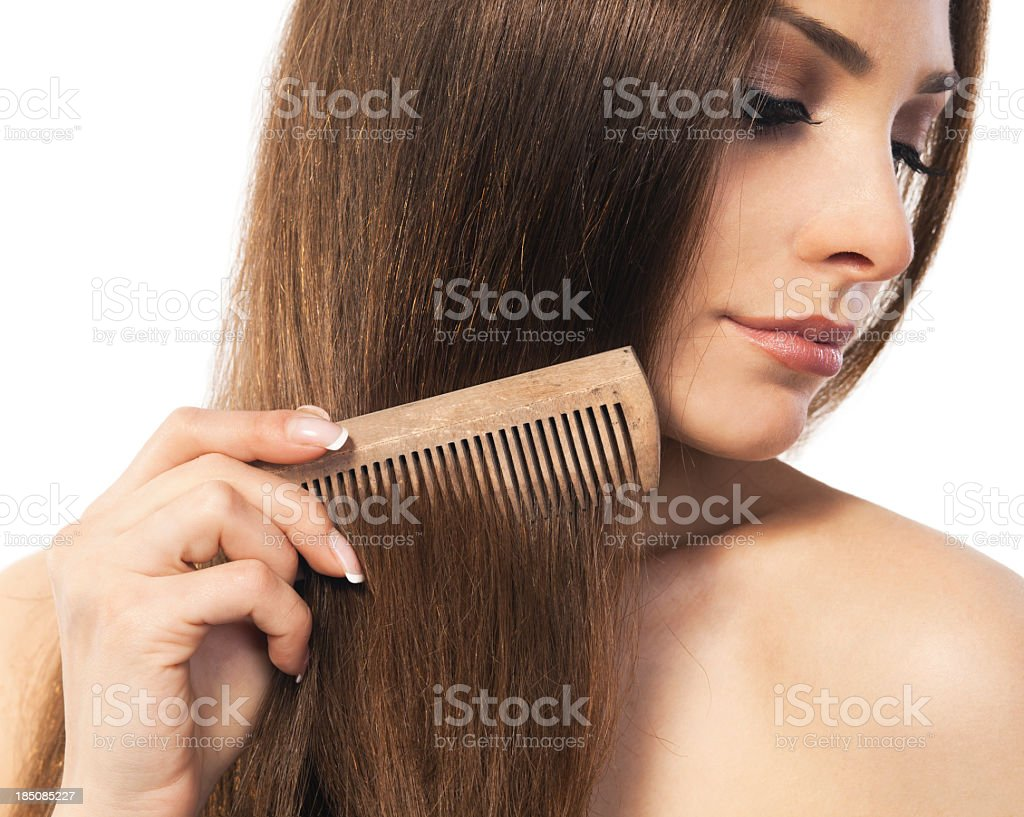 Young brunette woman combing through her long hair stock photo