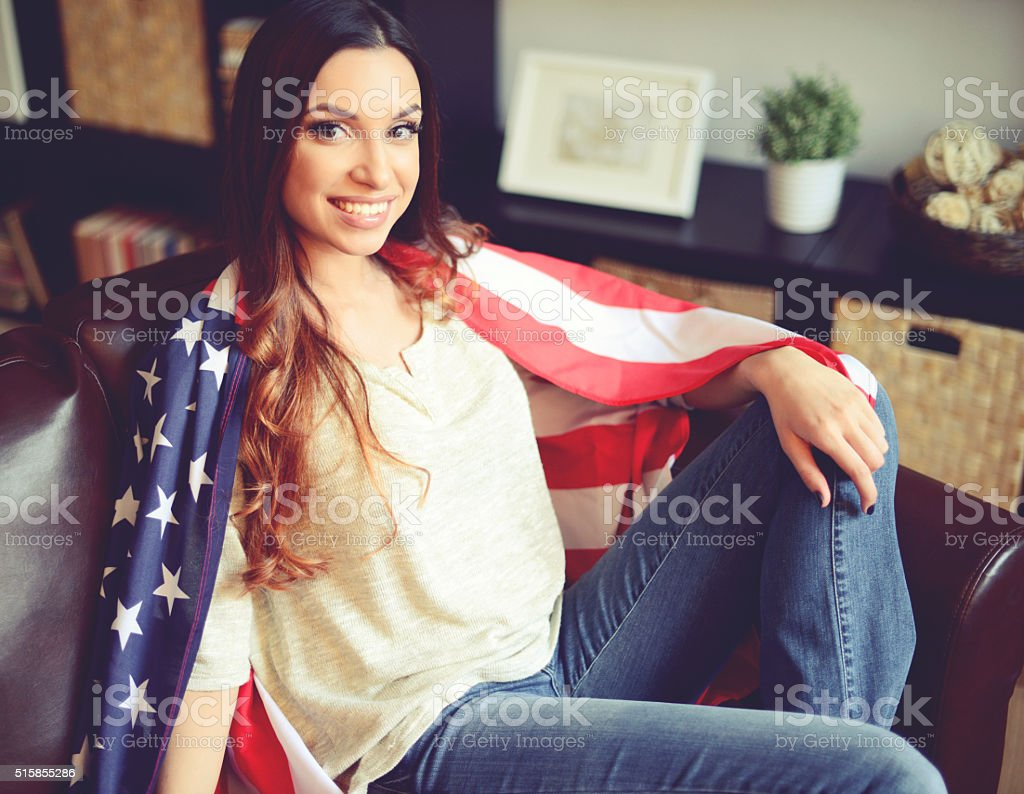 young brunette woman in home interior with American flag stock photo