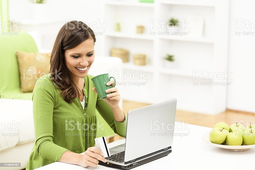 Young brunette woman is e-banking at home stock photo