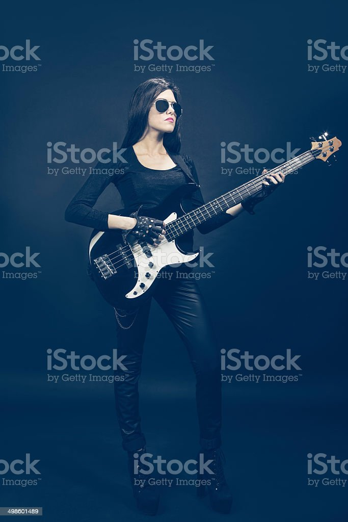Young brunette woman playing bass royalty-free stock photo