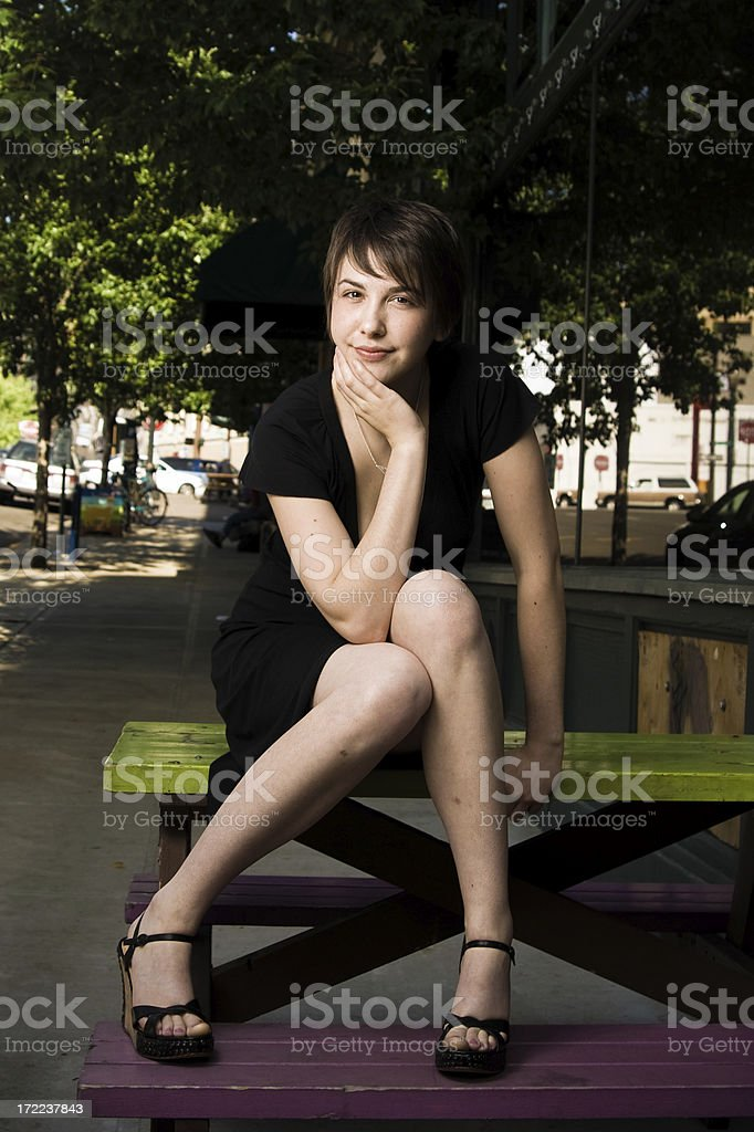 young brunette woman posing downtown stock photo