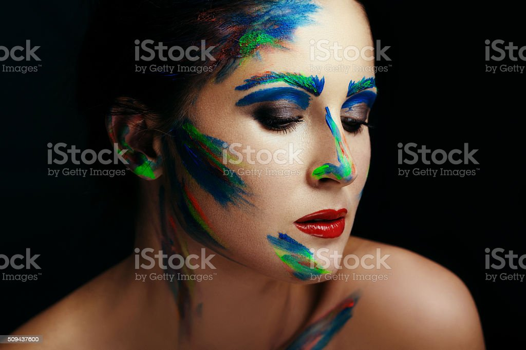 Young brunette woman posing with colorful paint brush strokes stock photo