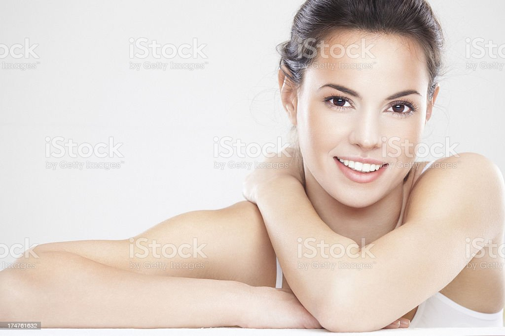 Young brunette woman with beautiful smile hugs herself stock photo