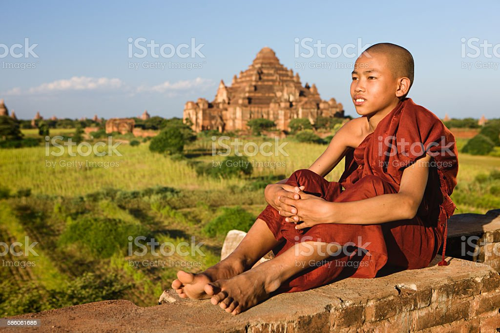 Young Buddhist monk looking at the Bagan's panorama stock photo
