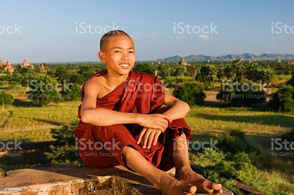 Young Buddhist monk resting on a temple stock photo