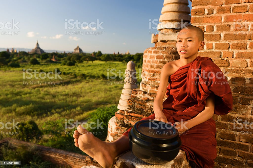 Young Buddhist monk resting on the temple, Bagan stock photo