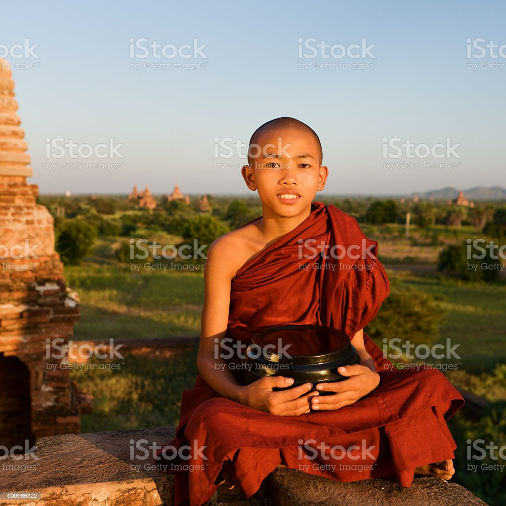 Young Buddhist monk sitting on the roof of temple. Bagan stock photo