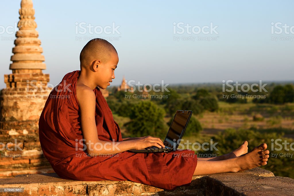 Young Buddhist monk using laptop, Bagan stock photo