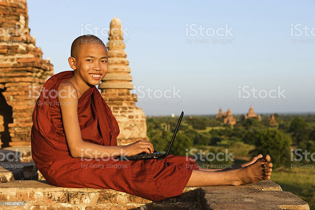 Young Buddhist monk using laptop stock photo