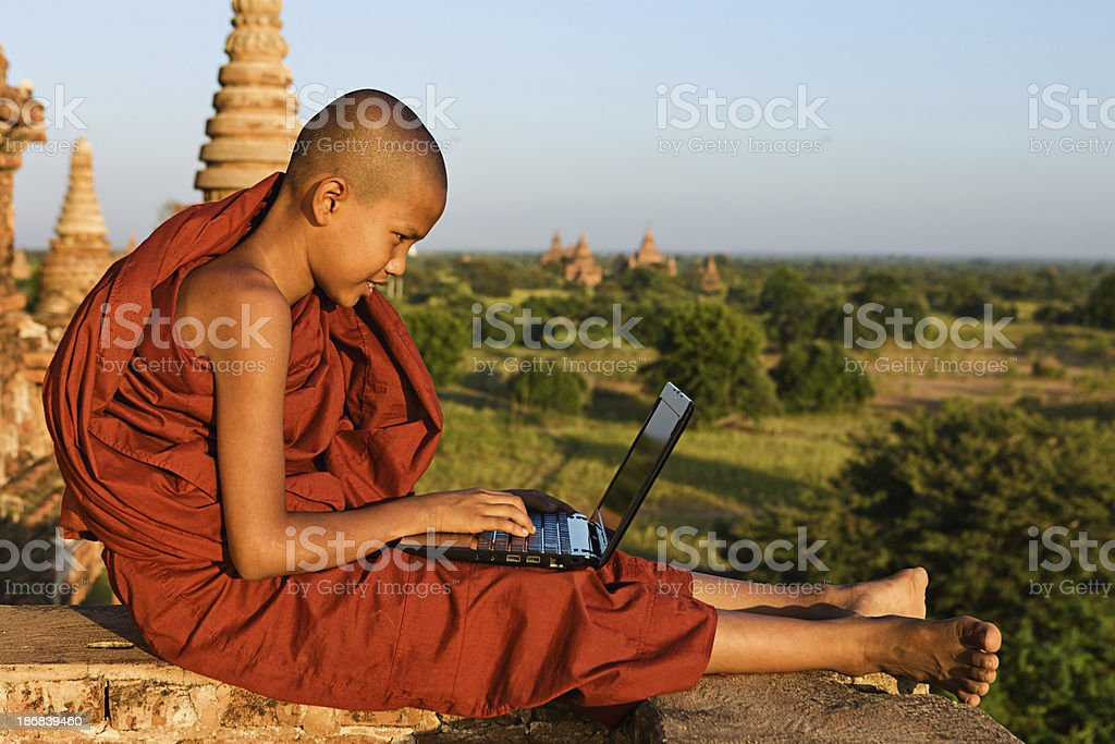 Young Buddhist monk using laptop royalty-free stock photo