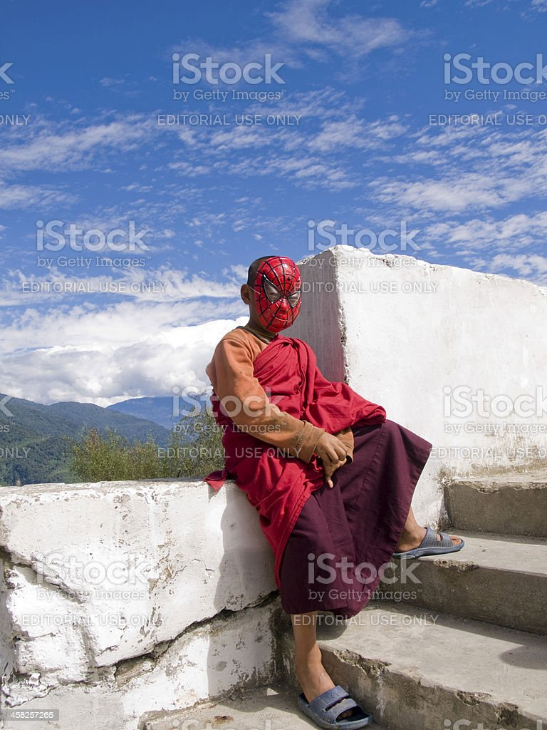 Young Buddhist monk with spiderman mask royalty-free stock photo