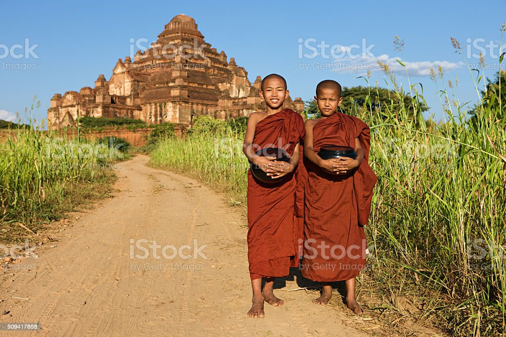 Young Buddhist monks walking along the road stock photo