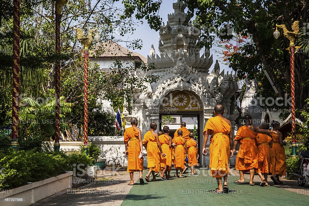 Young buddhist monks walking in the temple ground stock photo