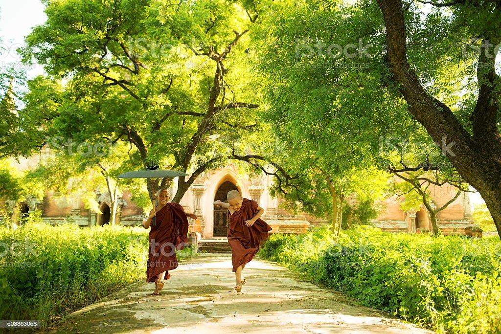 Young Buddhist novice monks running outside monastery stock photo