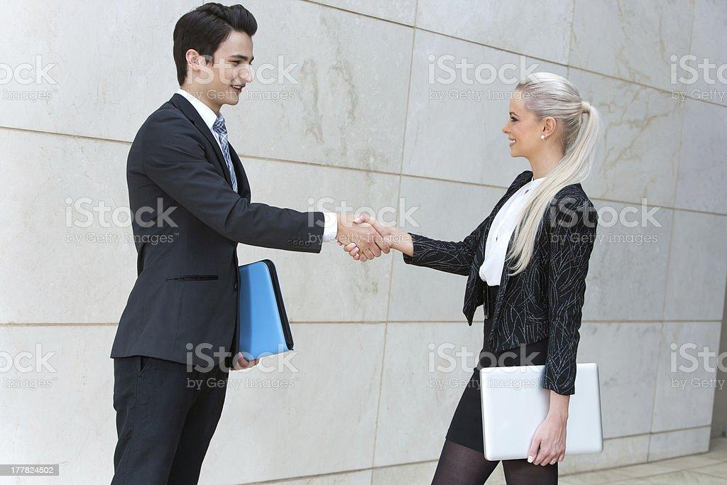 Jeune couple d'affaires se serrant la main au-dessus de contrat. photo libre de droits